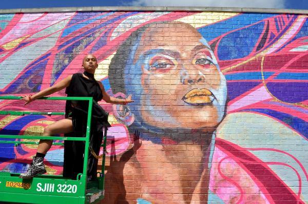 Person in flowing black dress, posed before a mural of themself, in blues, pinks, greens, & golds.