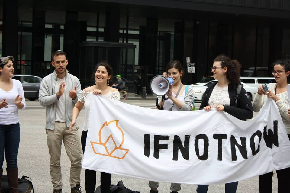 "Several humans standing behind an ""IfNotNow"" banner, on a city street."