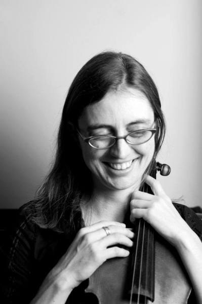 Black & white portrait of Ammie, smiling and looking downwards, cradling a viola.