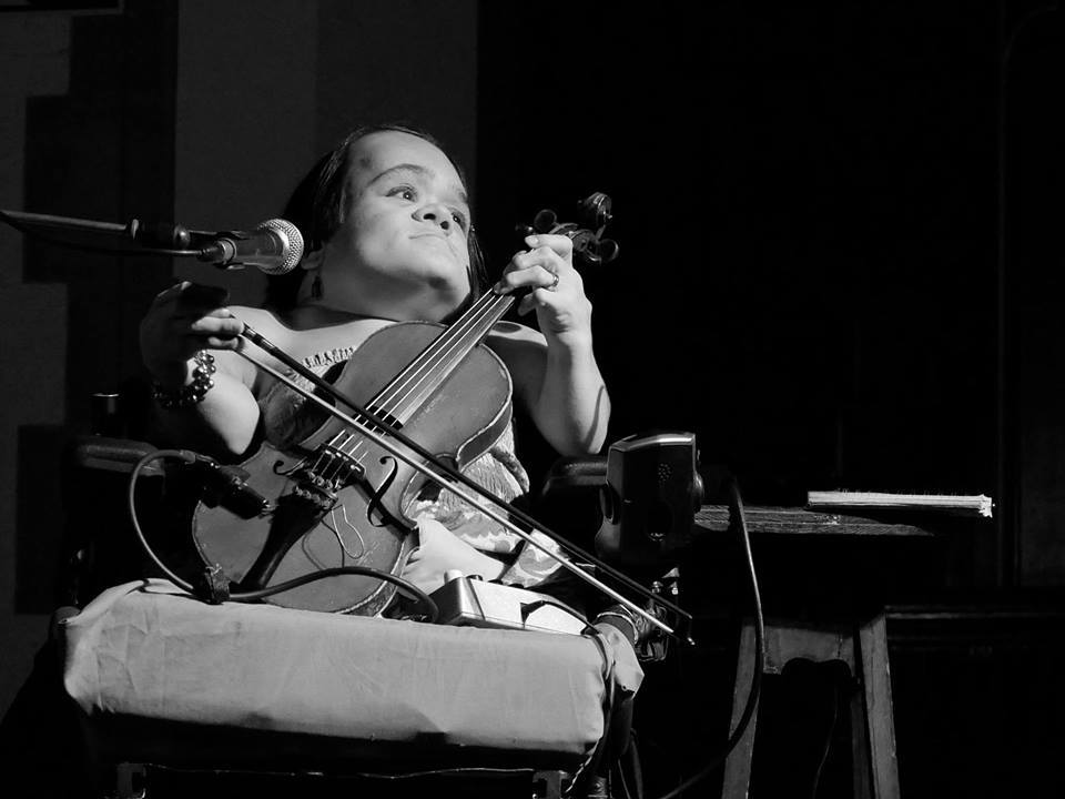 Black and white photo of Gaelynn Lea, playing their instrument.
