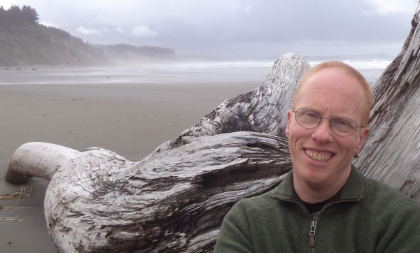 Headshot of Eli Clare, large piece of driftwood and misty beach in background.
