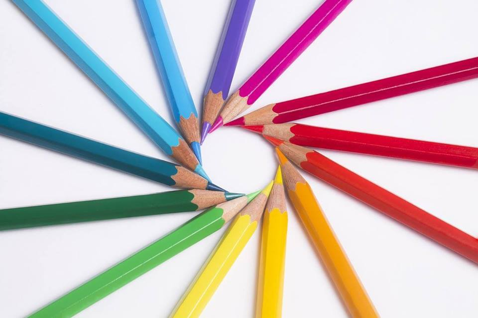 Colored pencis neatly laid out in a spiral pattern, forming a circle with their tips.